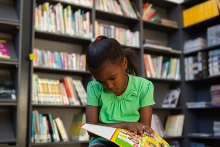 Front view of a focused cute African American schoolgirl reading a book in the library at school