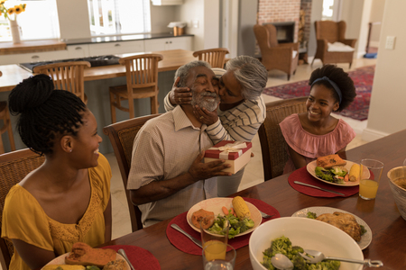 Side view of African American senior woman kissing her husband surrounded by his daughter and his grand daughter for his birthday while sitting at the dining table at home 写真素材