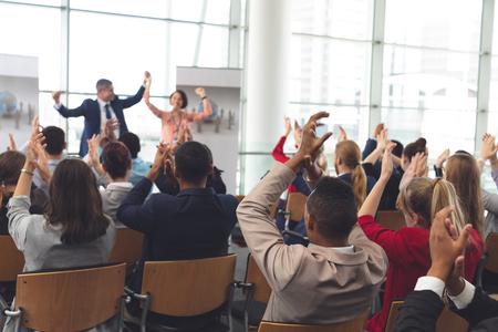 Rückansicht verschiedener Geschäftsleute, die applaudieren und feiern, während sie vor multiethnischen Geschäftskollegen beim Geschäftsseminar im Bürogebäude sitzen