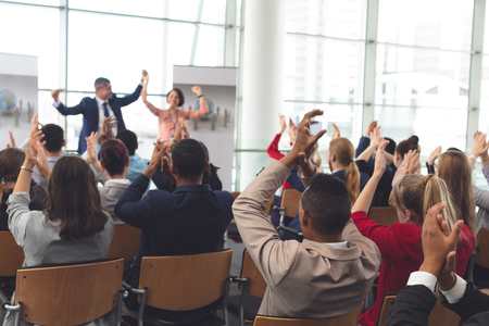 Rear view of diverse business people applauding and celebrating while they are sitting in front of multi-ethnic business coworkers at business seminar in office building