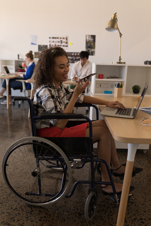 Side view of young disabled mixed-race female executive talking on mobile phone at desk in modern office