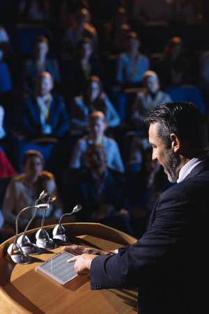 High angle view of Caucasian businessman standing and looking at digital tablet on stage in auditorium Standard-Bild - 121802374