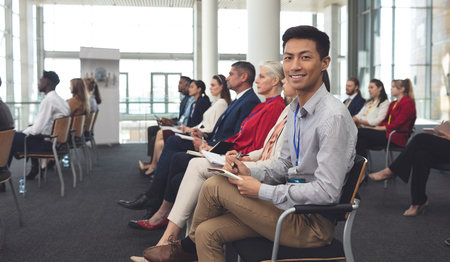 Side view of happy Asian businessman looking at camera at a business seminar in office building Imagens