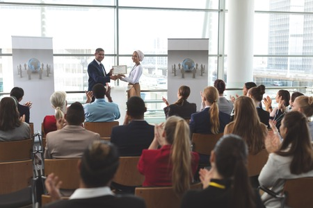 Front view of mixed race businesswoman receiving award from mixed race businessman in front of business professionals applauding at business seminar in office building Banco de Imagens