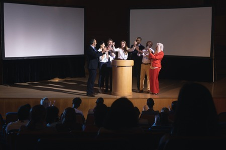 Front view of happy Caucasian businesswoman standing at the stage of the auditorium with colleagues in front of audience Foto de archivo