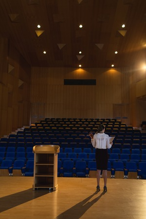 Rear view of blonde Caucasian businesswoman practicing and learning script while standing in the auditorium Imagens