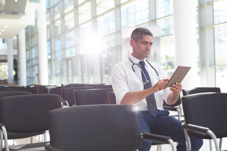 Front view of Caucasian male doctor sitting on chair and using digital tablet in conference room Imagens