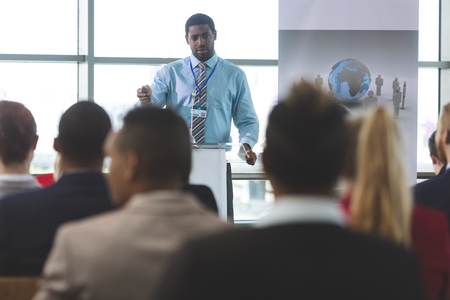 Front view of African-American businessman speaker speaking in a business seminar in modern office building
