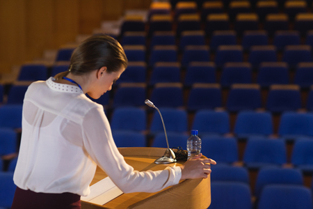Side view of blonde Caucasian businesswoman looking in script  and trying to speak in the empty auditorium 免版税图像