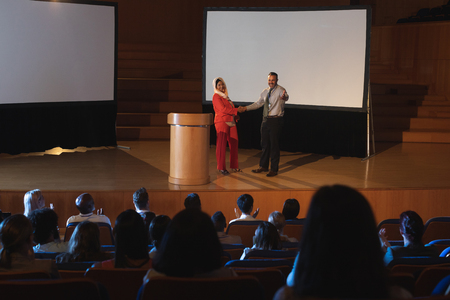 High view of mixed race business colleague standing and discussing with each other in front of the audience in auditorium while shaking hand Imagens