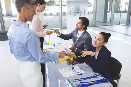 Zijaanzicht van diverse zakenmensen die inchecken aan de conferentieregistratietafel in de kantoorlobby