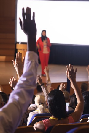 Rear view of mixed race audience raising hand for asking question in the auditorium