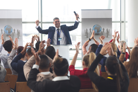Rear view of diverse group of business people applauding and celebrating while they are sitting in front of mixed race businessman at business seminar