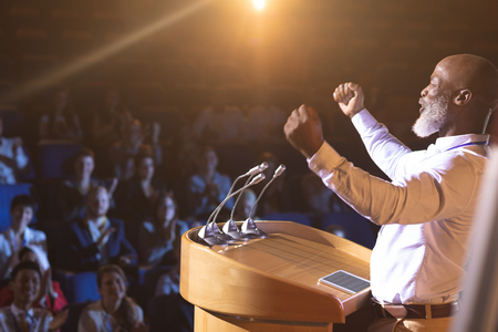 Side view of old African-American businessman standing near podium and giving speech to the audience in the auditorium