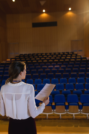 Rear view of blonde Caucasian businesswoman practicing and learning script while standing in the auditorium 版權商用圖片