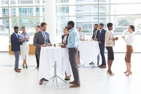 Vista frontal de diversos empresarios interactuando entre sí en la mesa en el vestíbulo de la oficina