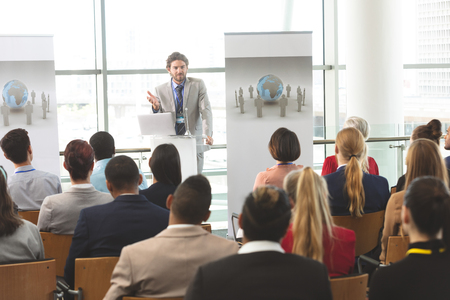 Front view of Caucasian businessman with laptop speaks in front of diverse crowd of business people at business seminar in office building