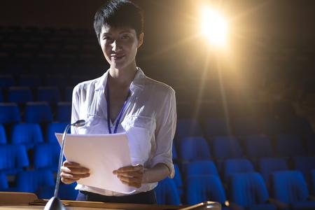 Vorderansicht der jungen asiatischen Geschäftsfrau, die auf dem Podium auf der Bühne im Auditorium steht, während sie die Kamera mit orangefarbenem Licht im Hintergrund betrachtet Standard-Bild
