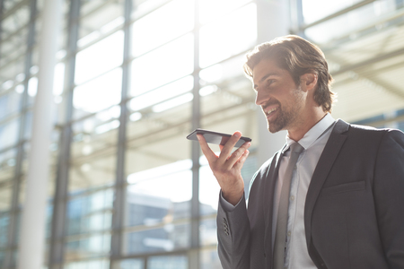 Low angle view of happy young Caucasian businessman talking on mobile phone in lobby office Stock Photo