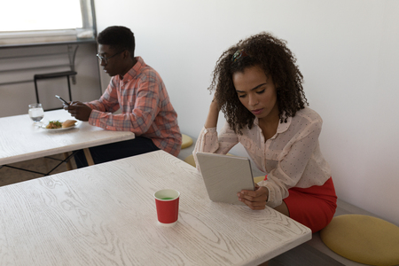 Side view of African-American male and mixed-race female executives using electronic devices in canteen at office