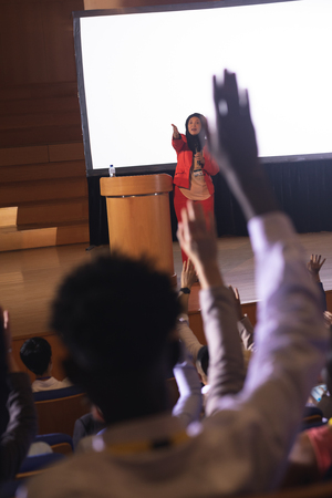 Front view of mixed race businesswoman listening and asking while audience raising hand for the queries in the auditorium