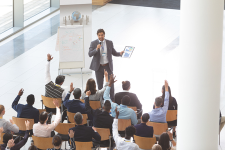 High angle view of middle-aged Caucasian businessman speaking and holding digital tablet and microphone at business seminar with interactive group of diverse business people listening in conference room.
