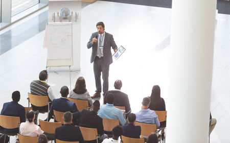 High angle view of middle-aged Caucasian businessman speaking in front of group of  diverse business people while holding microphone and digital tablet in conference