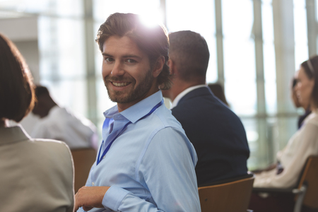 Portrait of happy young Caucasian businessman looking at camera during seminar in office building Stok Fotoğraf - 122297207