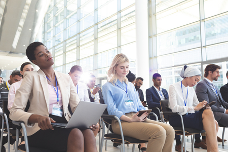 Front view of diverse business people attending a business seminar in a conference room. with black businesswoman holding a laptop on foreground Stok Fotoğraf