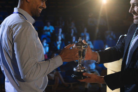 Side view of Caucasian businessman giving trophy to mixed race business male executive on stage in auditorium Stok Fotoğraf - 122297209