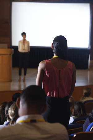 Rear view of mixed race woman from the audience standing and asking query in the auditorium Stok Fotoğraf - 122297211