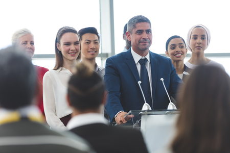 Front view of mixed race businessman standing on podium with diverse colleagues and speaking at business seminar in office building Stok Fotoğraf