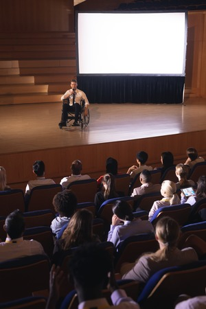 High view of Caucasian businessman sitting on a wheelchair and giving presentation to the audience in the auditorium