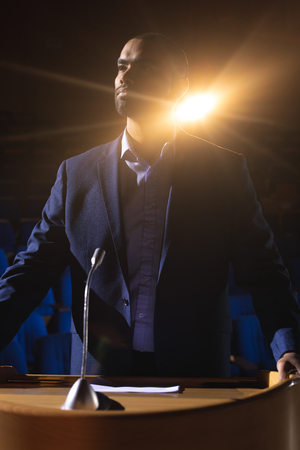 Front view of handsome mixed race businessman standing on stage in auditorium. Businessman thinking