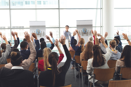 Rear view of diverse business people raising hands at business seminar while Asian businessman points at someone to give them a turn to speak Stock Photo