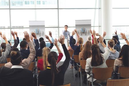 Vue arrière de divers hommes d'affaires levant la main lors d'un séminaire d'entreprise tandis qu'un homme d'affaires asiatique désigne quelqu'un pour lui donner la parole Banque d'images