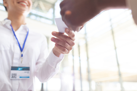 Close-up of diverse business people exchanging business card in conference Imagens
