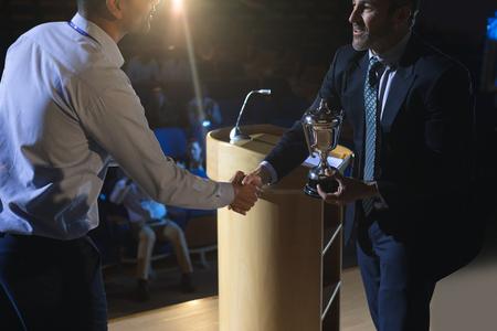 Seitenansicht eines kaukasischen Geschäftsmannes, der auf der Bühne im Auditorium einen männlichen Geschäftsleiter mit gemischten Rennen schätzt