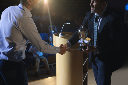Side view of Caucasian businessman appreciating mixed race business male executive on stage in auditorium