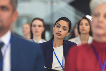 Front view of attractive young mixed race businesswoman looking thoughtful while attending business seminar in office Imagens