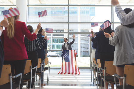 Front view of Caucasian businessman speaks while diverse business people moving american flag in a business seminar in office building