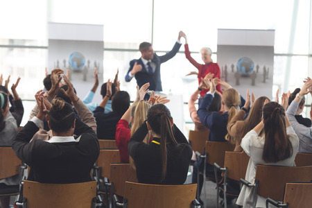 Rear view of diverse business people applauding and celebrating while they are sitting in front of multi-ethnic business executives at business seminar in office building