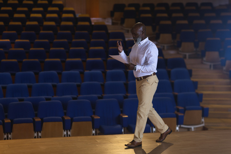 Side view of old African-American businessman with holding script walking in a auditorium