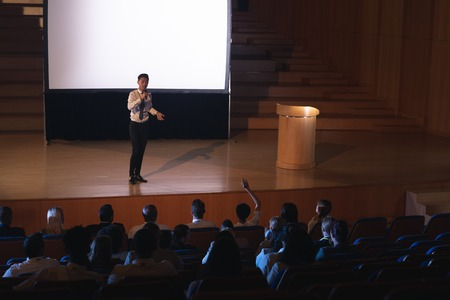 High view of young Asian businessman standing and giving presentation in auditorium while audience raising hand for asking query Stok Fotoğraf