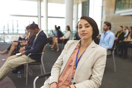 Front view of young mixed race businesswoman looking at camera during seminar in office building