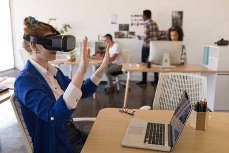 Side view of young Caucasian businesswoman using virtual reality headset at desk in modern office Imagens