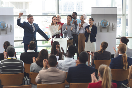 Front view of mixed race businessman standing on podium with diverse colleagues clapping as he speaks at business seminar in office building