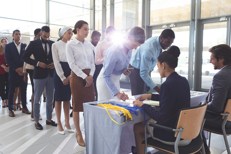 Front view of pretty Caucasian businesswoman and handsome African American businessman signing in at conference registration table while group of diverse business people standing in queue in lobby