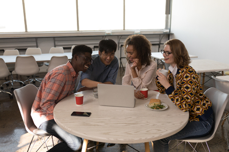 Front view of young diverse business colleagues discussing over laptop in modern office Imagens