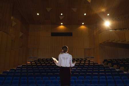 Rear view of beautiful Caucasian businesswoman practicing and learning script while standing in the auditorium Stock Photo